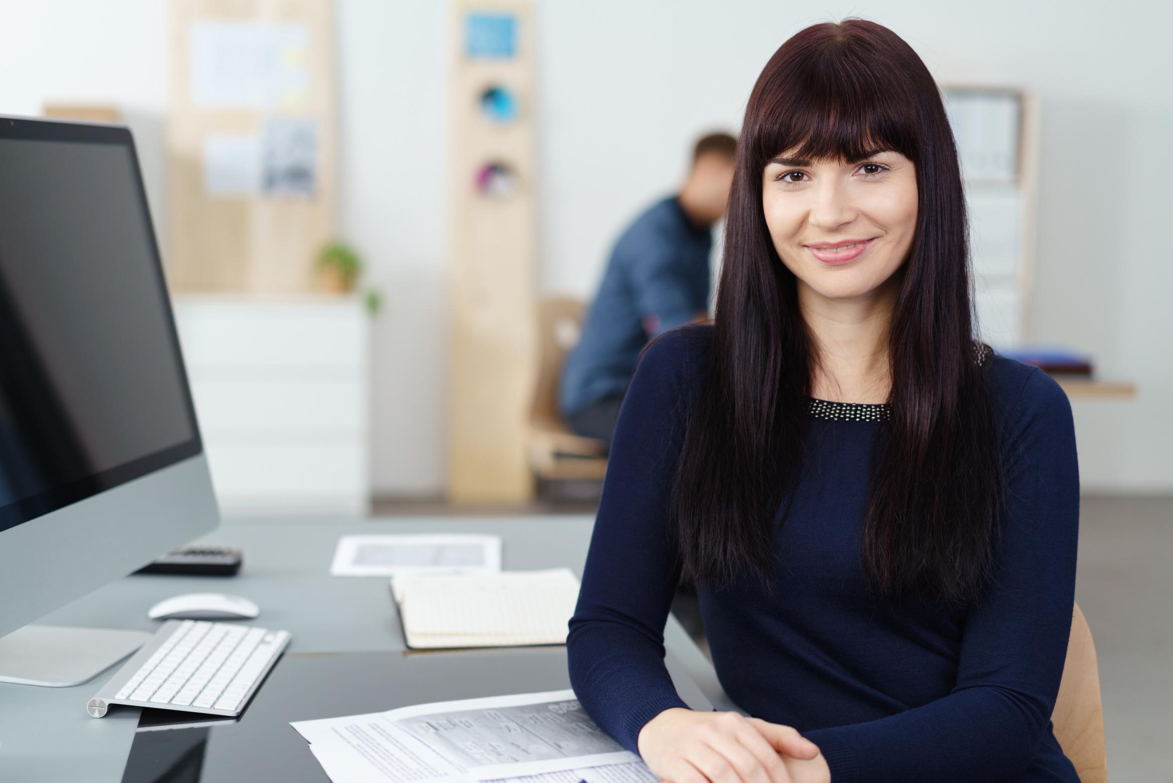 freundliche mitarbeiterin arbeitet im büro am pc